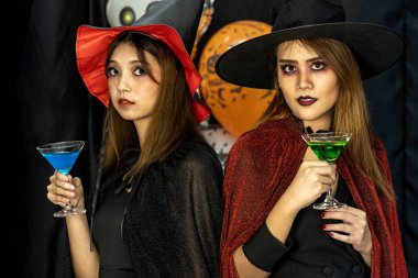 Two young adult and teenager girls celebrating a Halloween party carnival Festival in Halloween costumes drinking alcohol cocktail