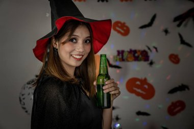 Young adult and teenager girl celebrating a Halloween party carnival Festival in Halloween costumes drinking alcohol beer