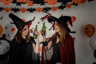 Two young adult and teenager girl celebrating a Halloween party carnival Festival in Halloween costumes drinking alcohol beer