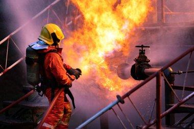 Su sisi tipi yangın söndürücü kullanan itfaiyeci petrol boru hattı sızıntısı ve petrol platformu ve doğalgaz istasyonundaki patlamayla savaşmak için. İtfaiyeci ve endüstriyel güvenlik kavramı.