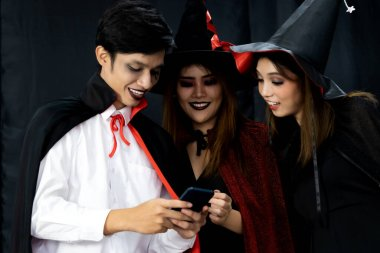 Group of friends asian young adult people see photo in mobile phone after take selfie photograph. They wear Halloween costume. Halloween celebrate and international holiday concept.