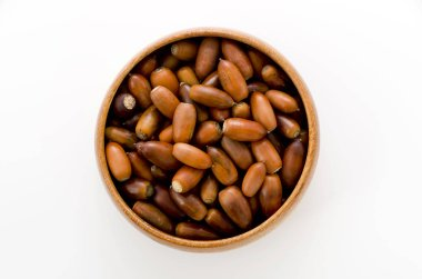 acorns in a wooden round bowl on white background