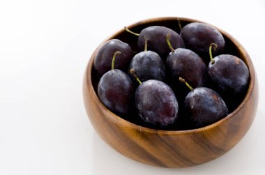 Fresh purple plums in wooden round bowl