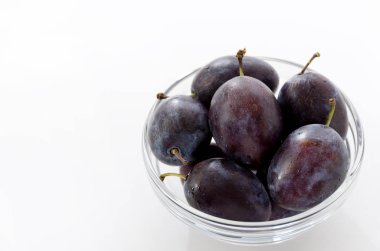 Fresh purple plums in round bowl