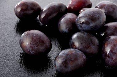 Fresh purple plums on black Stone plate