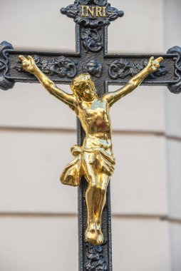 Crucifixion monument with black cross and golden Chris at Saint Karl Cathedral in Vienna, Austria, details