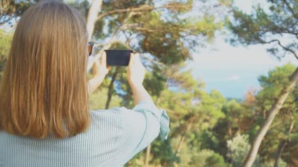 Frau nimmt Bilder der Natur mit dem Handy
