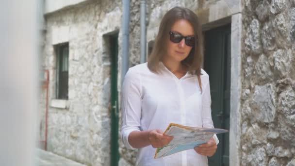 Mladá blondýnka s mapou v ulici.