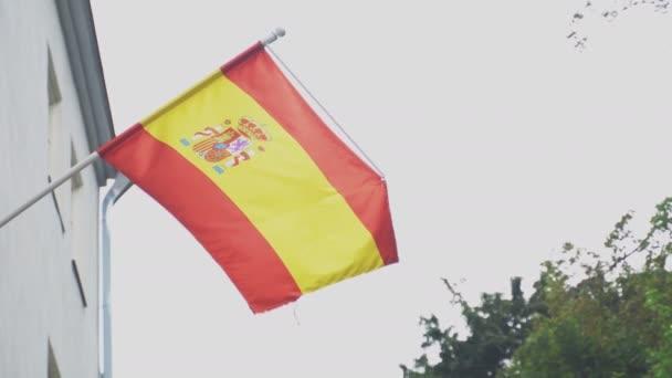 Spanish flag on a flagpole waving on house.