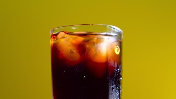 Glas Cola mit Eiswürfeln auf gelbem Hintergrund.