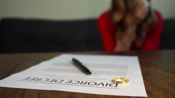 Dokument o rozvodu. Žena pláče na pozadí.
