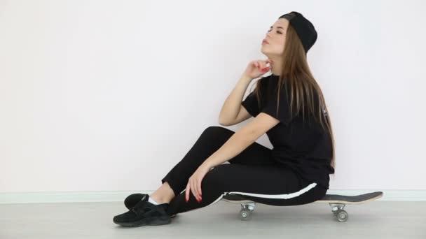 dospívající dívka v módní hip hop oblečení a čepici vystupují proti bílé zdi se skateboard