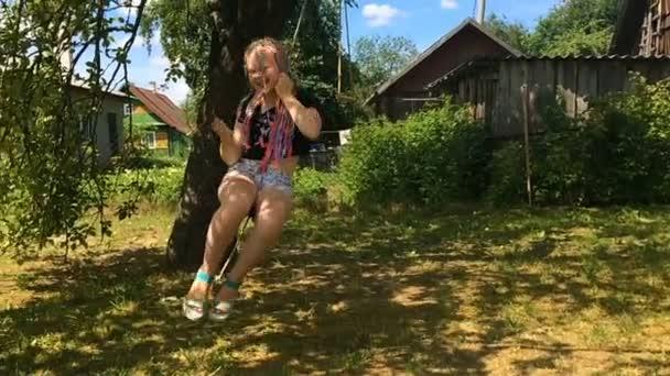 glückliches Mädchen schaukelt auf einer Scheune im rustikalen Garten - Zeitlupe