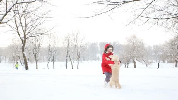 láska pro domácí zvířata - veselá žena tance a má legraci s pejskem v parku zasněženou zimní