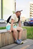 modern élet a nagyvárosban - sportos fiatal férfi a városban egy padon pihenő