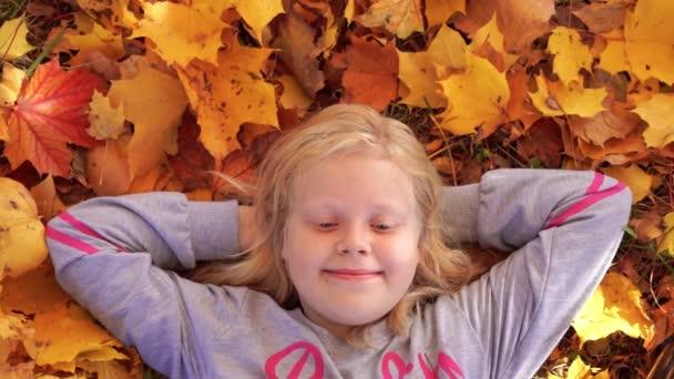 Porträt eines schönen Mädchens im Herbst Park Porträt eines schönen Mädchens im Herbst Park auf abgefallenen Blättern