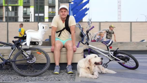 modern life in a big city - sporty young man with dog resting on a bench in the city after a bike ride