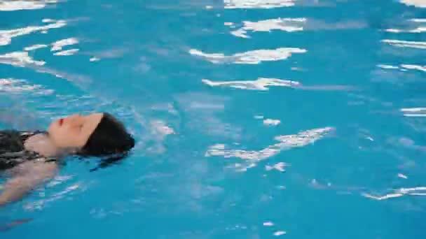 Schwimmkurse für Kinder im Pool - schönes hellhäutiges Mädchen schwimmt im Wasser