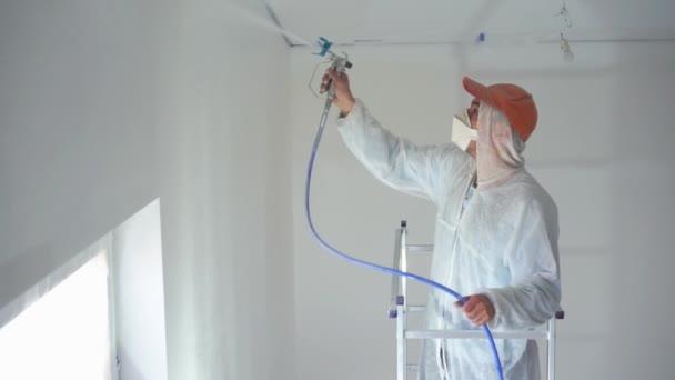 Schönheit in Zeitlupe. Reparatur der Wohnung - professioneller Maler streicht die Wände mit weißer Farbspritzpistole