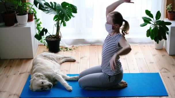 Zuhause bleiben. Frau macht während Quarantäne Yoga im Wohnzimmer, ein großer Hund liegt in der Nähe. Zeitraffer
