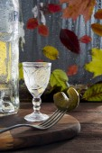 Photo On a wooden table, lit by the sun, lies a cutting board on which stands a crystal glass with vodka. Nearby is a bottle and a fork with a chopped pickle. In the background, outside the wet window, over