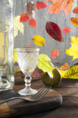 Photo On a wooden table, lit by the sun, lies a cutting board on which stands a crystal glass with vodka. Nearby is a bottle and a fork with a chopped pickle. In the background, behind a wet window, leaf fa