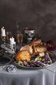 Az asztalon van egy tálca egy halom bárány átszúrta a kardot. A közelben van pohár bor és gyertya bronz gyertyatartókkal. A rózsák mögött, és egy tál alakú koponya a vér.