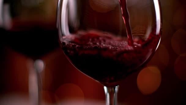 Superzeitlupe, in der Rotwein aus der Flasche in den Becher geschüttet wird. aufgenommen mit High-Speed-Kinokamera mit 1000fps 4k Auflösung.