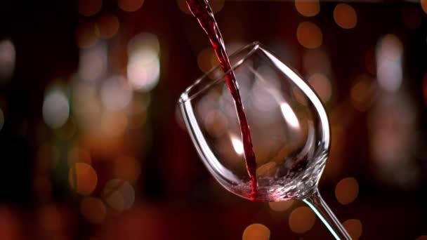 Super zpomalené nalévání červeného vína z láhve do poháru. Pořízené vysokorychlostní kamerou kino s 1000fps 4k rozlišením.