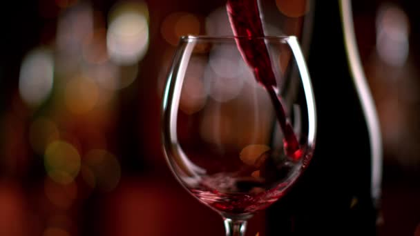 Super slow motion di vino rosso di versamento dalla bottiglia in calice. Girato con telecamera cinema ad alta velocità con risoluzione 1000fps 4k