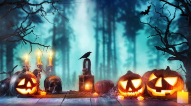 Scary horror background with halloween pumpkins jack o lantern, placed on wooden deck. Halloween spooky background.