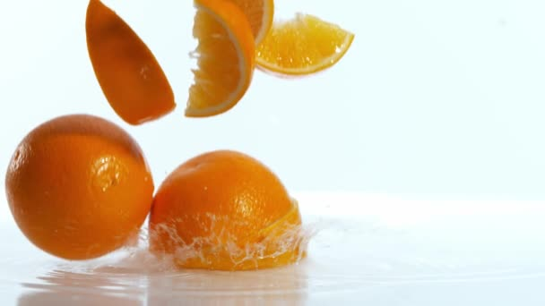 Super slow motion of falling pieces of oranges, isolated on white background. Filmed on high speed cinema camera, 1000 fps.