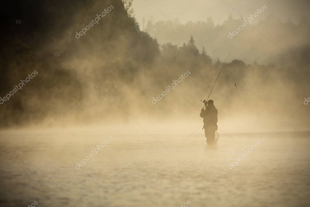 Fisherman holding fishing rod, standing in river, misty fog around. Beautiful sunrise light. Outdoor activities and spending leasure time