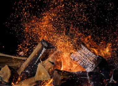 Burning wooden logs in fire, campfire isolated on black background