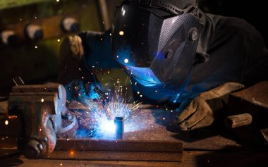 Welder working in workshop factory. Heavy industrial and manual working concept