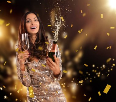 Beautiful young brunette woman holding goblet of champagne and splashing bottle of wine. Celebration and sucess concept.