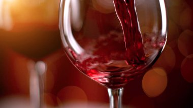 Freeze motion of pouring red wine from bottle into goblet. Low depth of focus