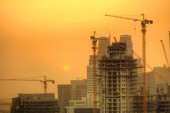 Construction zone with cranes building skyscrapers in sunset light. New and modern architecture building structure in Dubai city, UAE.