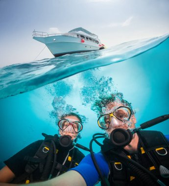Split photography of safari yacht, woman and man diver exploring coral reef. Underwater fauna, flora and marine life.