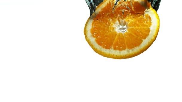 Super pomalý pohyb padající oranžové plátky, izolovaný na bílém pozadí. Natáčeny z vysokorychlostní filmové kamery, 1000 fps.
