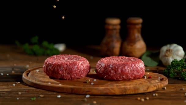 Hackfleisch-Hamburger mit fallendem Gewürz mit seitlicher Bewegung auf dem Schieberegler. Gefilmt mit High-Speed-Kinokamera, 1000fps.