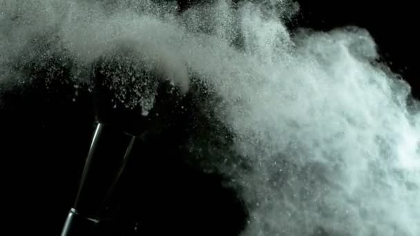 Super pomalý pohyb make-upu kartáč s padajícím stříbrným práškem, černé pozadí. Natočeno na vysokorychlostní kameře, 1000fps.