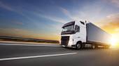 Evropské nákladní auto na dálnici s krásným západem slunce obloha a dramatické mraky. Doprava a nákladní téma, volný prostor pro text.