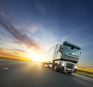 European truck on motorway with beautiful sunset sky and dramatic clouds. Transportation and cargo theme, free space for text. stock vector