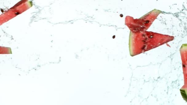 Super zpomalený pohyb kousků melounu, které se vznášejí ve vzduchu se stříkajícími vodami. Natočeno na vysokorychlostní kameře, 1000 fps.