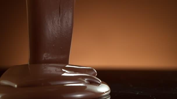 Super zpomalený pohyb nalití tmavé horké čokolády na tmavý stůl. Natočeno s kamerou s vysokou rychlostí