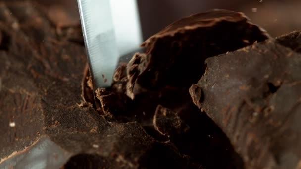 Super pomalý pohyb odřezávání tmavých kousků čokolády dlátem. Natočeno vysokorychlostní kamerou, 1000fps.