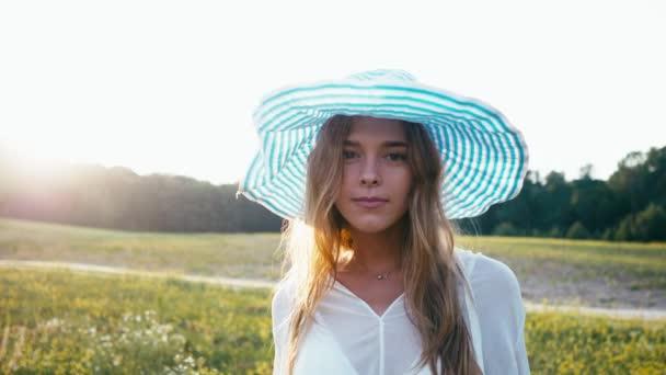 Schönheit lächelndes Mädchen auf dem Frühlingsfeld. Wiese. Porträt einer lachenden und glücklichen jungen Model-Frau mit gesunden langen Haaren, die die Natur genießt. schöne junge Frau im Freien