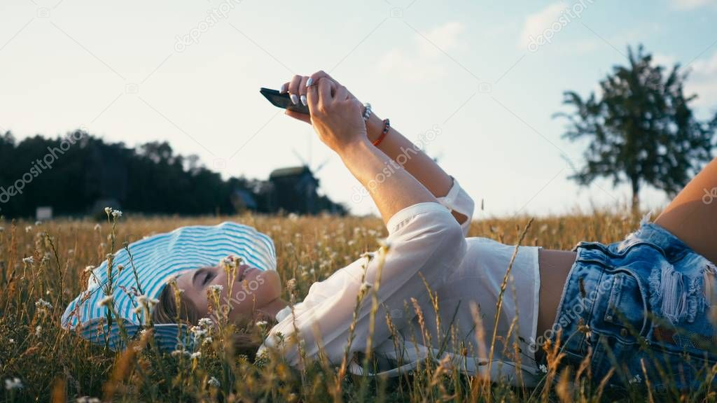 Woman in the Summer Park Using Mobile Phone. Authentic Creative Shot
