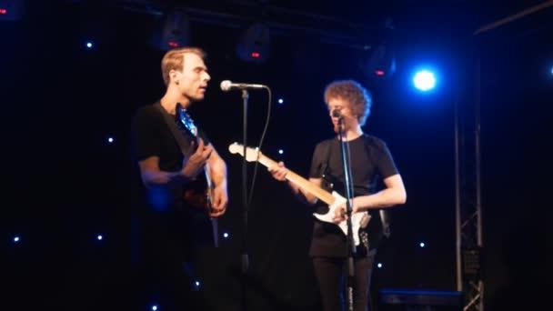 Koncert a rock zenekar teljesít a színpadon, két elektromos gitár énekesek. Punk zene video, nehéz fém- vagy rock csoport. Lassú mozgás hangszerjáték két férfi együttes